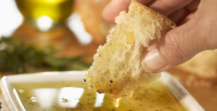 Hand Dipping a Piece of Bread into Olive Oil